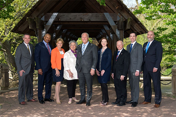 The 2019 Naperville Mayor and City Council pose in front of a covered bridge on the Naperville Riverwalk.